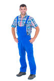 Handyman in coveralls standing hands on hip over white background Royalty Free Stock Image