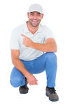 Handyman crouching while pointing on white background Stock Photography