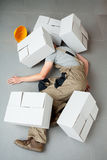 Handyman crushed by cartons Stock Photos