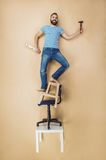 Handyman in a dangerous pose Stock Photo