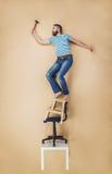 Handyman in a dangerous pose stock image