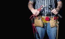 Handyman detail on black. Detail of handyman with leather toolsbelt and tools on dark background Stock Photos