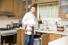 Handyman doing some work in a kitchen Royalty Free Stock Photos