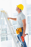 Handyman with drill machine climbing ladder in building. Side view of handyman with drill machine climbing ladder in building Royalty Free Stock Photos