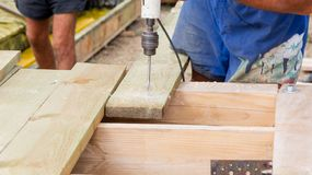 Handyman drills holes in the board. At construction site royalty free stock images