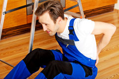 Handyman fell from a ladder and sitting on the floor with backache Stock Images