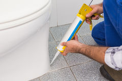 Handyman filling in tiles in bathroom Stock Photography