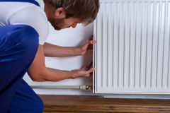 Handyman fix the radiator. In the room stock photography