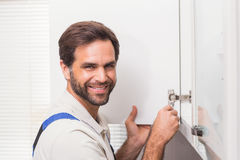 Handyman fixing the cupboard Royalty Free Stock Image