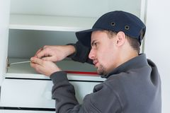 Handyman fixing cupboard in kitchen Royalty Free Stock Images