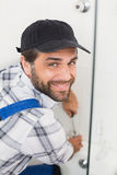 Handyman fixing door with screwdriver Royalty Free Stock Photos