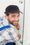 Handyman fixing door with screwdriver Royalty Free Stock Photos