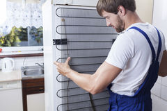 Handyman fixing the fridge Stock Images
