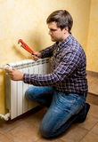 Handyman fixing heating radiator with red plumber pliers Stock Photography