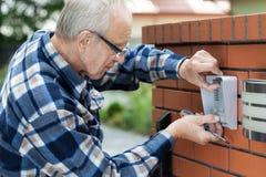 Handyman fixing intercom Royalty Free Stock Photography