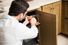 Handyman fixing a kitchen cabinet. Point of view of a young handyman using a power drill to fix a door in a kitchen cabinet royalty free stock photo