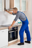 Handyman Fixing Kitchen Extractor Fan Stock Images