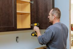 Handyman fixing kitchen& x27;s cabinet with screwdriver. Adjusting fixing door kitchen cabinets royalty free stock photo