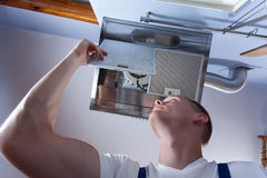 Handyman fixing kitchen wall hood Stock Image