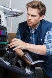 Handyman fixing printer according to manual stock photo