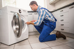 Handyman fixing a washing machine Stock Image