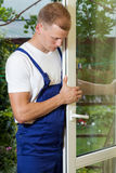 Handyman fixing a window wing Stock Images
