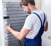 Handyman and fridge repair Stock Photos