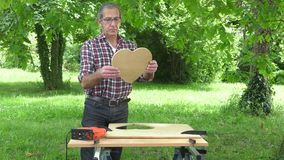The Handyman gets the heart he just saw. Man finish cutting a heart in a panel of wood particles stock footage