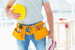 Handyman with gloves and helmet at construction site Royalty Free Stock Image