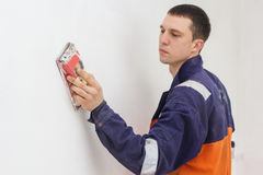 Handyman grinding with sandpaper on a white wall. Handyman is doing repair works with sandpaper on a white wall Stock Photo