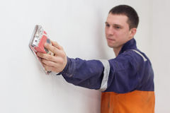 Handyman grinding wall with sandpaper. Handyman is doing grind works with sandpaper on a white wall Stock Images