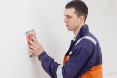 Handyman grinding wall with sandpaper. Handyman is doing repair works with sandpaper on a white wall Stock Photos