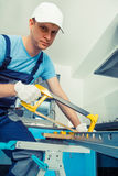 Handyman with a hacksaw. Handyman with cap and protective gloves on using a hacksaw to cut a steel plank Stock Photos