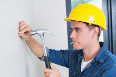 Handyman hammering nail in wall Stock Images