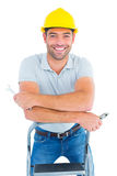 Handyman with hand tools on step ladder Stock Image