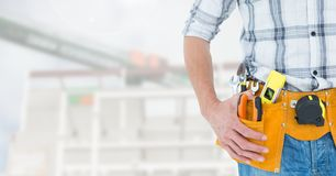 Handyman with hands on hip and tool belt Stock Images
