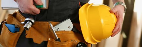 Unknown handyman with hands on waist and. Handyman with hands on waist and tool belt with construction tools against wood background. DIY tools and manual work royalty free stock image