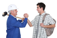 Handyman handshaking his trainee. Stock Images
