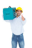 Handyman in hard hat with toolbox gesturing thumbs up Stock Photos