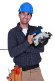 Handyman holding a circular saw. Stock Photo