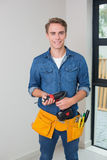 Handyman holding a drill with toolbelt around waist Royalty Free Stock Image