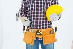 Handyman holding hard hat and hammer Stock Image