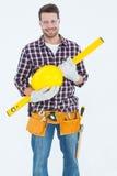 Handyman holding hard hat and spirit level Royalty Free Stock Photo