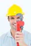 Handyman holding monkey wrench against white background Stock Images