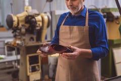 Handyman holding one luxury shoe royalty free stock photo