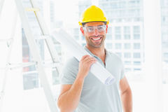 Handyman holding rolled up blueprint in bright office Royalty Free Stock Image