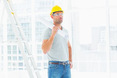 Handyman holding rolled up blueprint in bright office Royalty Free Stock Images