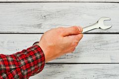 Handyman holding wrench in hand. Male person, repairman or mechanic, in classic checkered work shirt is holding wrench in his hand. Rough skin, worn shirt. Close Stock Photos