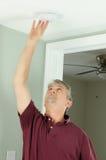 Handyman home owner checking smoke alarm testing Royalty Free Stock Photo