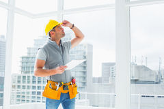 Handyman inspecting building. Handyman holding clipboard while inspecting building Stock Image